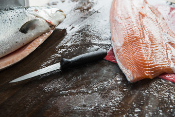 Filleting knife next to fresh salmon fillet on wooden cutting board