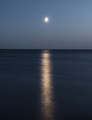 white moon over the sea with a reflection and a path