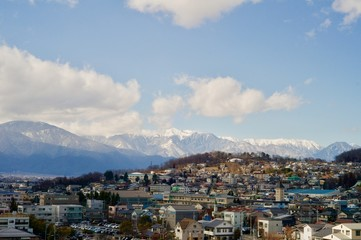 北アルプスの山々を背景にする住宅街