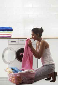 Young woman smelling clean towels from laundry basket in front of washing machine