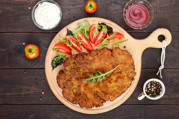 A large Viennese schnitzel  and tomato salad on a cutting board on a dark wooden background. Top view.
