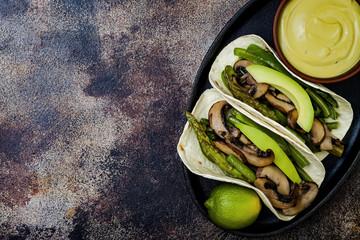 Grilled portobello, asparagus, bell peppers, green beans fajitas. Poblano mushroom tacos with jalapeno, cilantro, avocado crema. Vegan tacos with green summer vegetables. Copy space