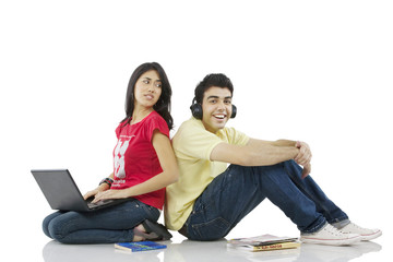 Girl sitting with a laptop while boy listens to music