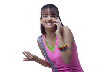 Happy young woman using cell phone while gesturing over white background
