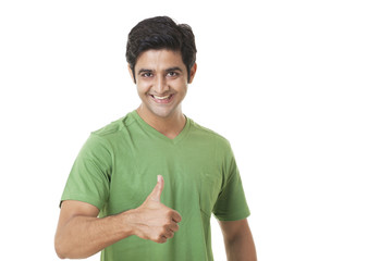 Portrait of happy young man giving you thumbs up on white background