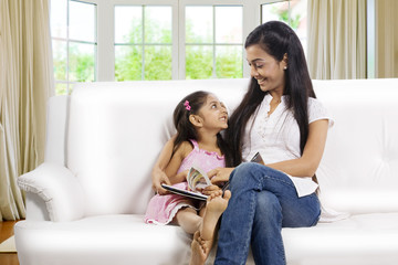 Mother and daughter sitting together with a story book
