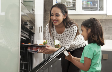 Young mother and daughter baking cupcakes into an oven