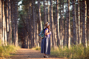 Happy senior woman in a straw hat with backpack walking through the forest. Nature outdoor activity. Healthy lifestyle concept.