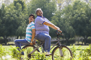 Father riding a bicycle while son sits behind