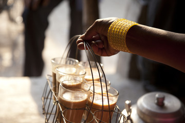 Close-up of female's hand holding tray of fresh morning chai