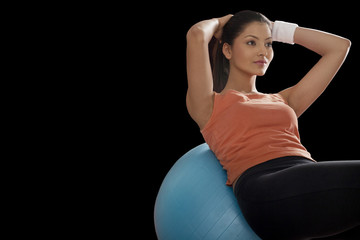 Fitness young woman balancing on exercise ball with hands behind head over black background