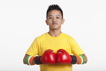 Portrait of confident young boy wearing red boxing gloves over white background