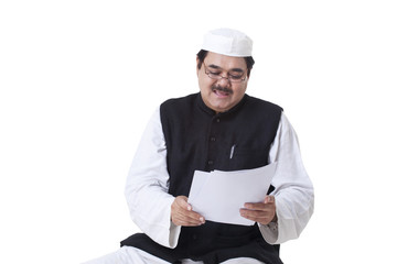 Politician in traditional clothes reading documents
