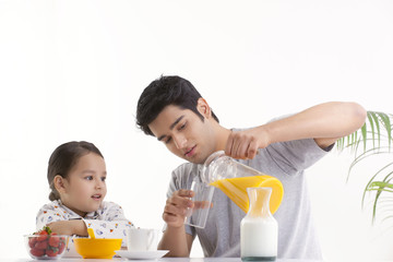 Father and young daughter having breakfast together
