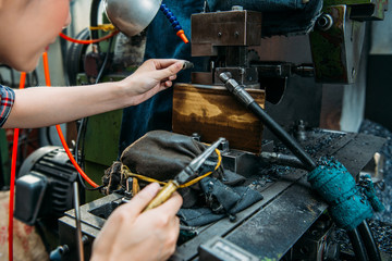 factory staff place parts in milling machine