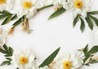 Flat lay frame made of white peonies, big leaves of iris isolated on white background. Top view holiday concept.
