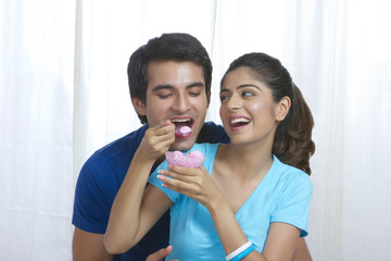Smiling young woman feeding man ice-cream at home