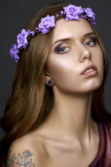 Beautiful model girl with a stylish hair and make-up in a bright roses flowercrown on a dark background