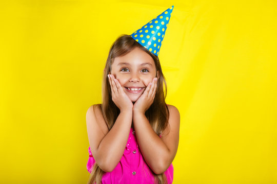Studio portrait of a little girl wearing a party hat on her birthday