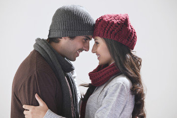 Young couple smiling at each other over grey background