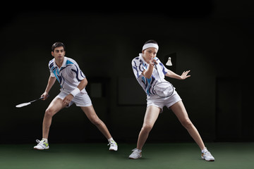 Players playing badminton doubles at court