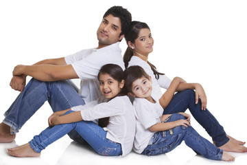 Portrait of happy family sitting over white background