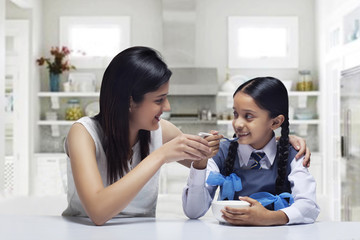 Mother feeding daughter breakfast at home