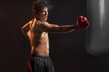 Male boxer hitting punching bag over black background