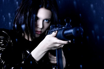 Sexe secret agent or assassin. Brunette girl dressed in leather and latex with gun on dark background