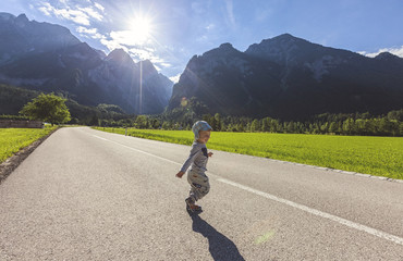 Little boy running on street surrounded by landscape and mountains