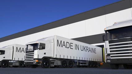 Freight semi trucks with MADE IN UKRAINE caption on the trailer loading or unloading. Road cargo transportation 3D rendering