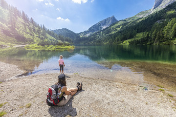 Girl and woman takes a rest at the Steirersee from hiking Tauplitzalm Austria