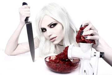 Beautiful and scaring witch woman in white with a knife and meat. Concept image for Halloween
