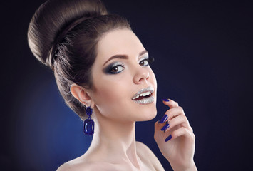 Makeup and manicure. Beauty portrait of young adorable looking brunette girl with high bun hairdo and glitter fashion makeup. Emotion and facial expression concept.