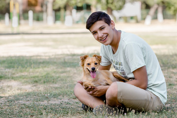 A teenager with a dog is playing fun