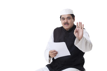 Male politician gesturing while reading document