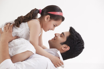 Girl sitting on father's stomach