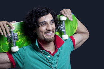 Close-up of cheerful young man holding skateboard behind head against black background