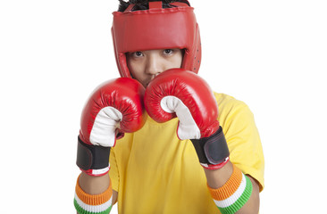 Portrait of boy wearing boxing gloves and head protector over white background