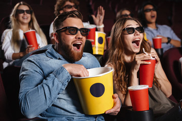 Laughing friends sitting in cinema watch film Wall mural