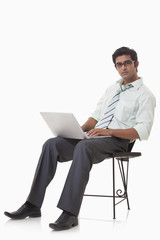 Portrait of handsome businessman on chair using laptop