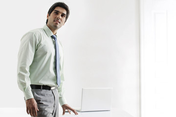 Confident businessman standing nearby laptop