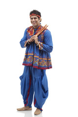 Full length portrait of happy young man in kedia and dhoti holding dandiyas over white background