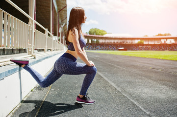 Portrait of a gorgeous girl doing squats in the stadium.