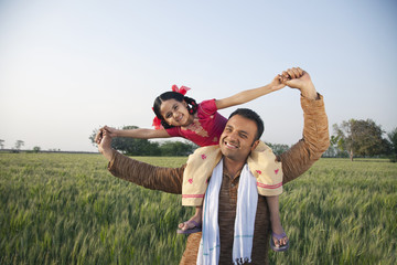 Portrait of a happy father carrying daughter on shoulders