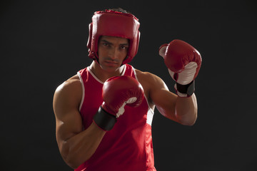 Portrait of an Indian male boxer wearing gloves and head protector isolated over black background
