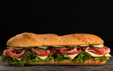 Wall Murals Snack Huge crispy baguette deli sandwich with meat and vegetables. Close up. Black background.