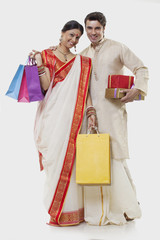 Portrait of a Bengali couple with shopping bags and gifts