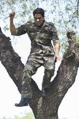 Aggressive soldier holding bayonet and jumping from the tree
