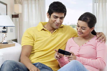 Young couple using cell phone while sitting on sofa